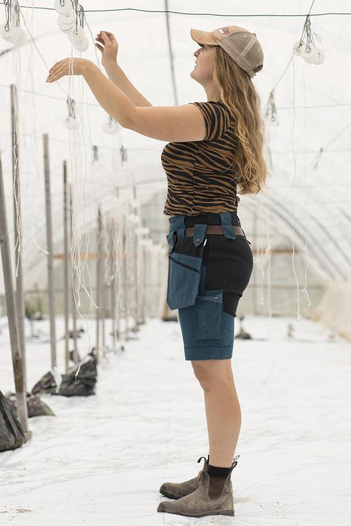 Kvinna i en odlingstunnel som lyfter på armarna när hon binder snören och bär korta, blå trädgårdsbyxor.