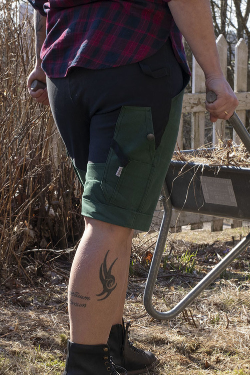 Kvinna i gröna trädgårdsbyxor som drar en skottkärra