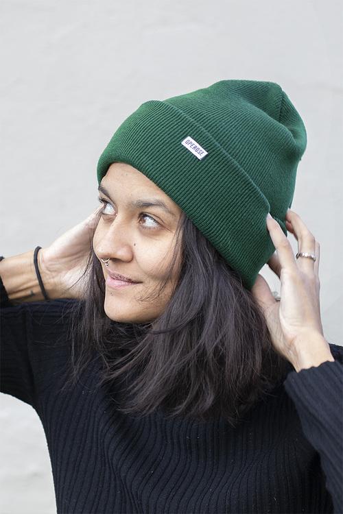 En kvinna som tittar uppåt och håller händerna på en grön mössa
