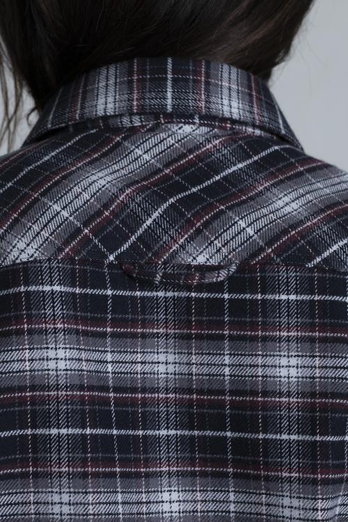 En närbild på oket på en arbetsskjorta med kvinnlig passfrom.