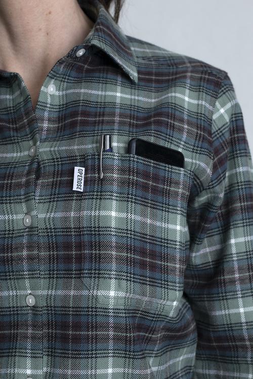 En bröstficka med en mobiltelefon och en penna som visar de fina färgerna på det rutiga tyget.