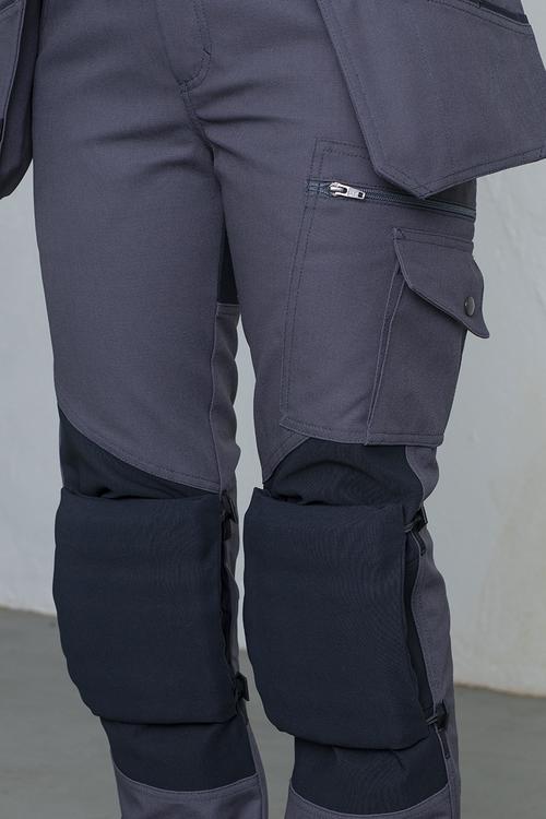 En arbetsbyxa där knäskydden sätts fast på utsidan.