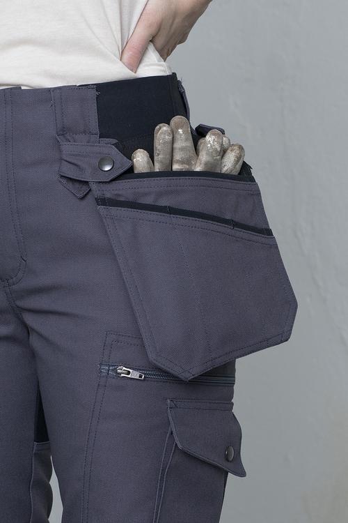Närbild på en trädgårdsbyxa som har en lös ficka med handskar istoppade.