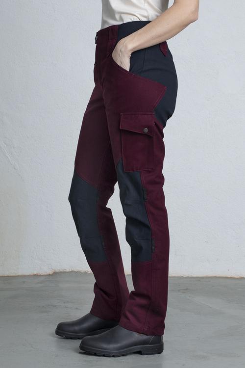 En kvinna i ett par vinröda arbetsbyxor står och lutar sig på ena benet.