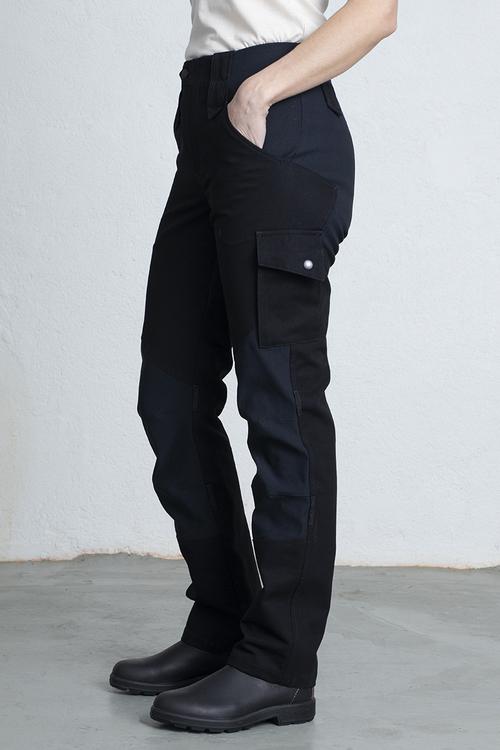 En kvinna står i ett par svarta arbetsbyxor med ena handen i fickan.