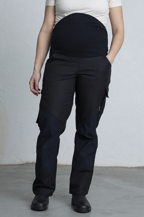 En gravid kvinna står i ett par arbetsbyxor med ena handen i fickan.