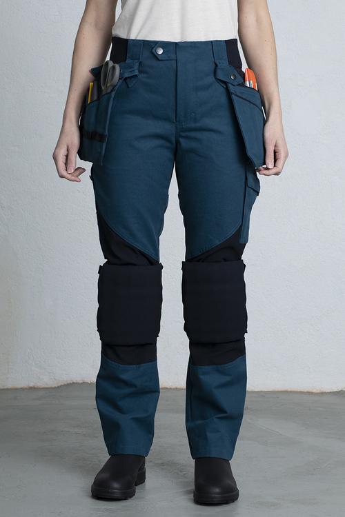 En petrolblå snickarbyxa med hängande fickor och knäskydd fastsatta vid knät.