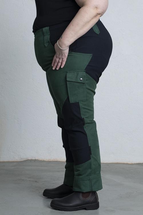 En kvinna i profil visar den stora storleken i trädgårdsbyxorna i grönt.