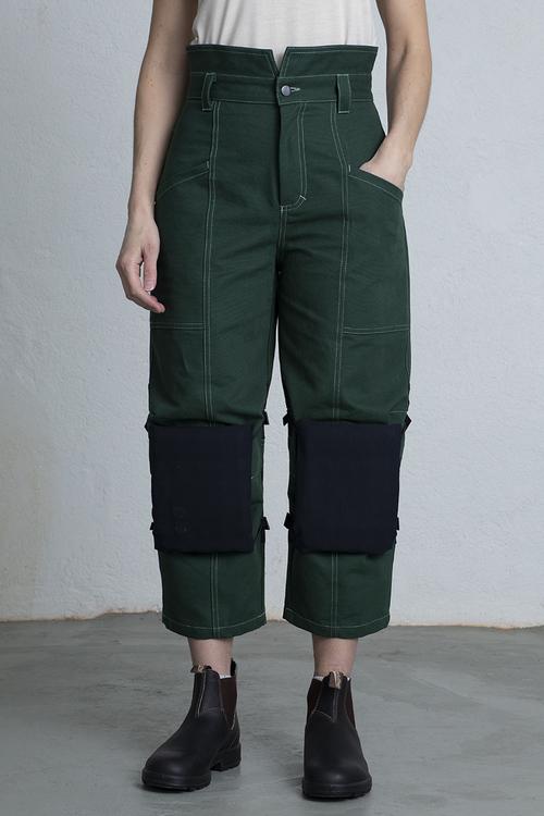 Kvinna med gröna snickarbyxor och svarta knäskydd.