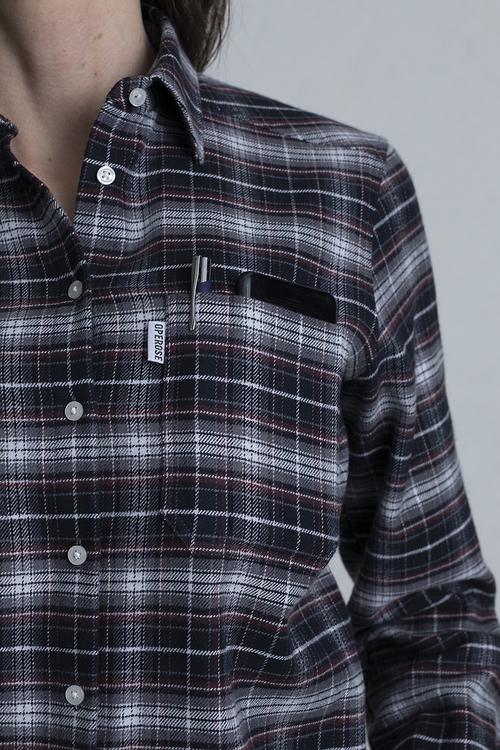 En närbild på en bröstficka på en flanellskjorta med svart bas. Fickan har en mobil och en penna istoppad.