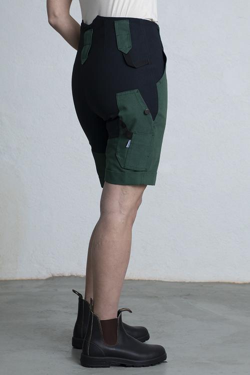 Arbetsshorts dam i grönt mot en vit vägg.