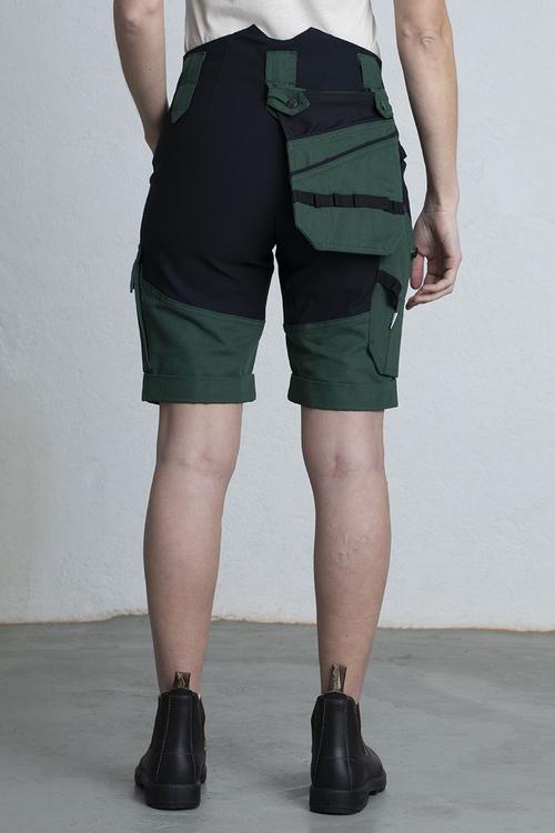 En kvinna står i ett par arbetsshorts med den hängande fickan flexibelt på baksidan för större rörelsefrihet.