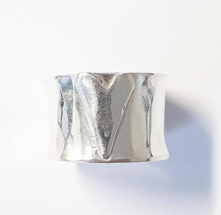 En bred hamrad silverring med handsågat hjärta