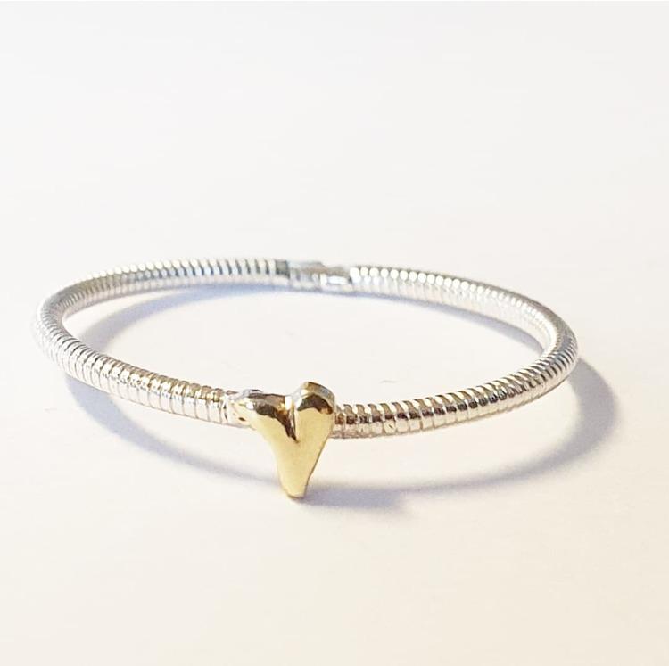En tunn silverring med handsågat hjärta i mässing