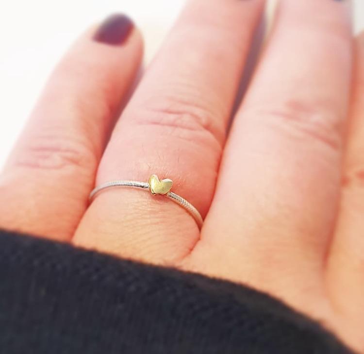 En tunn silverring med ett handsågat litet hjärta i mässing