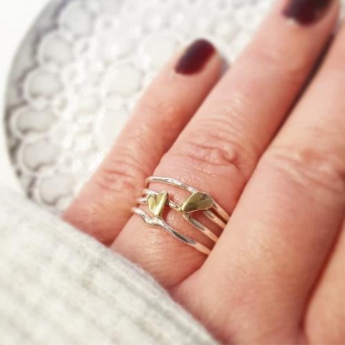 En bred luftig silverring med två handsågade hjärtan i mässing