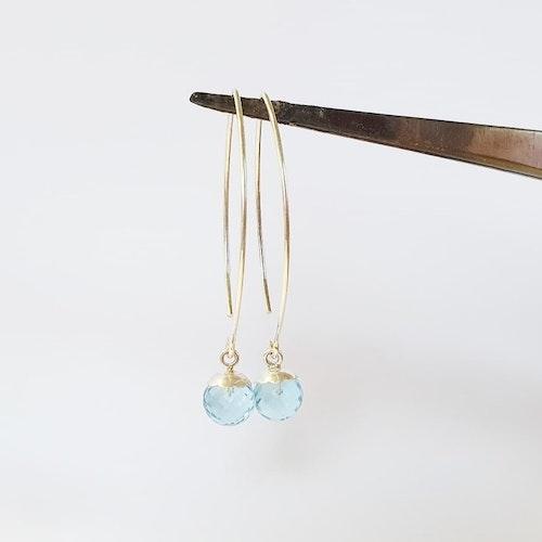 Örhänge i silver med facetterad blå topas på båge