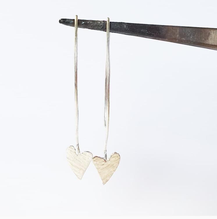 Örhänge med vackra hamrade silverhjärtan på båge