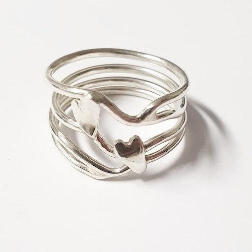 En luftig silverring med två handsågade hjärtan i silver