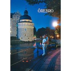 Vykort - Örebro -  Par framför Örebro Slott i kvällsljus