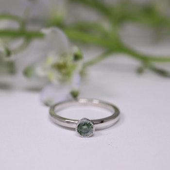 """""""Liljekonvalj"""" ring i vitt guld med en skogsgrön diamant"""