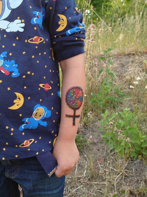 Feministisk tatuering i Prideflaggans vackra regnbågsfärger. Veganska och allergivänliga!