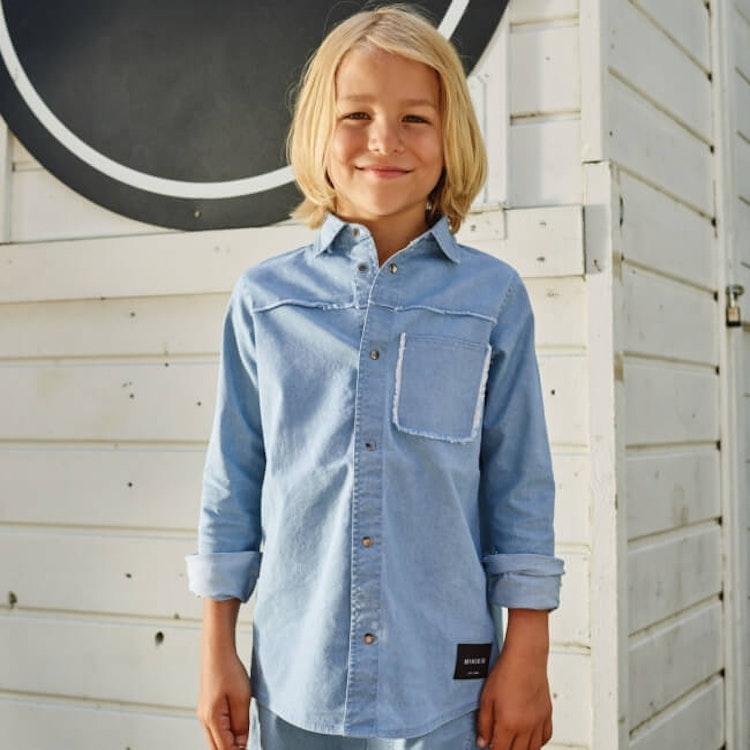 Barn klädd i ljusblå skjorta från MINIKID