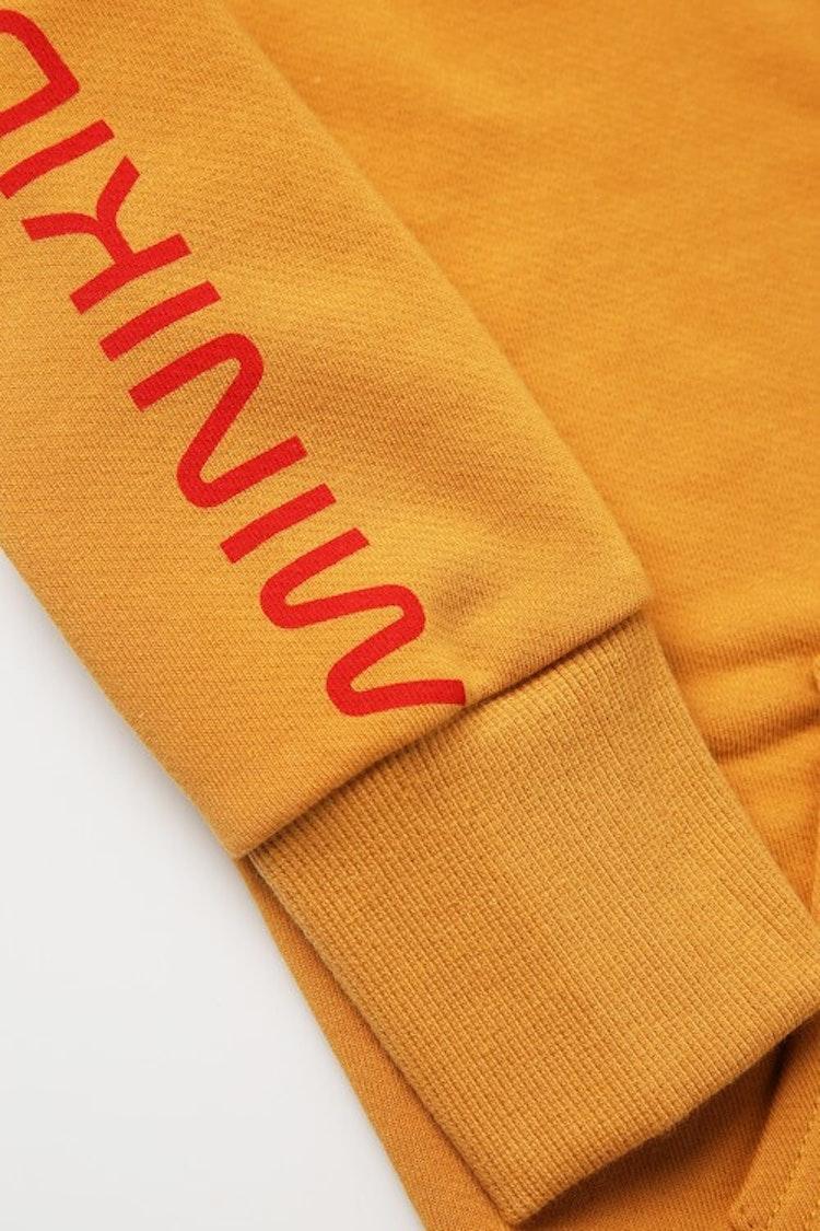 Tryck på ärmen på en gul luvtröja från MINIKID.