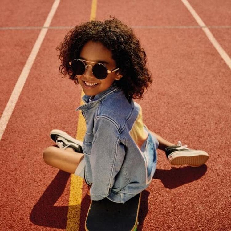 Ett barn i en ljusblå jeansjacka med ryggmärke från MINIKID.