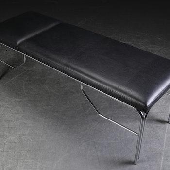 Undersökningsbrits i svart läder med kromad ställning