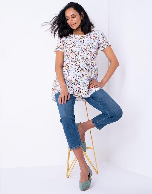 Blåa vadlånga gravidjeans med raka ben bild på modell med blommig topp sittandes