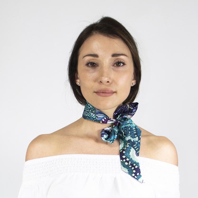 Twilly scarfette med blåa toner knyten runt en hals