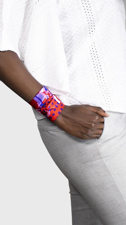 Twilly scarfette i rosa, blå och röd runt handleden