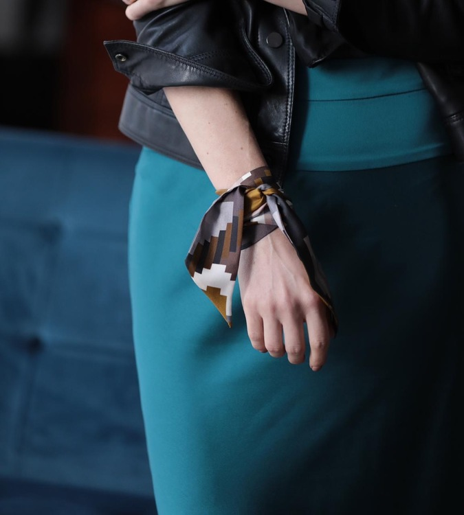 Twilly scarfette i guld och bruna färger runt en handled