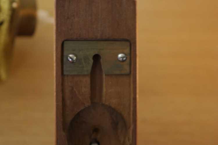 Vägglampa arm i teak med hängande kupa i glas närbild fäste