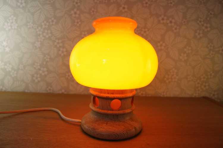 Bordslampa i orange glas och fot i furu tänd