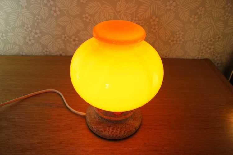 Bordslampa i orange glas och fot i furu tänd perspektiv