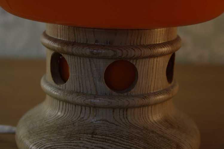 Bordslampa i orange glas och fot i furu närbild fot i furu