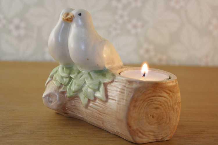 Ljusstake för värmeljus i keramik med två duvor som sitter på en pinne fotad från sidan