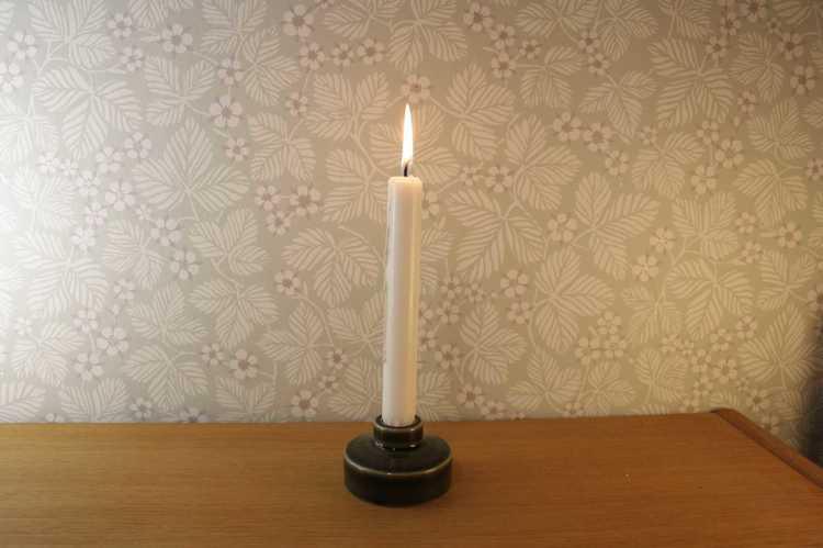 Liten grön cylinderformad ljusstake i keramik tillverkad av Wade i England med ett kronljus