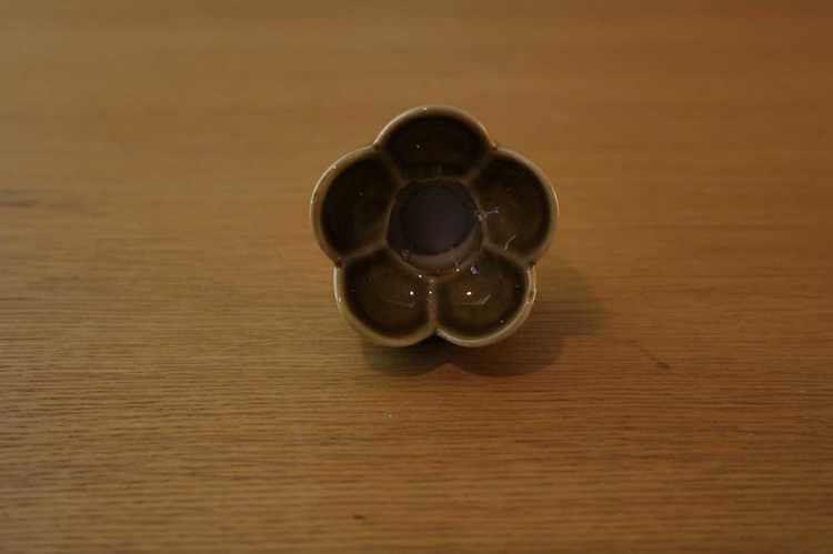 Bild tagen uppifrån på Liten ljusstake föreställandes en blomma från Wade i England med ett brinnande kronljus