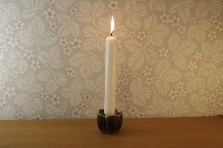 Liten ljusstake föreställandes en blomma från Wade i England med ett brinnande kronljus