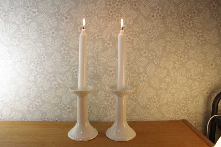Två stycken vita ljusstakar med brinnande kronljus av modell Tiara från Rörstrand