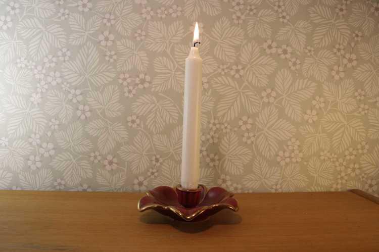 Vinröd ljusstake Röd Rubin av Arthur Percy för Gefle med ett brinnande kronljus