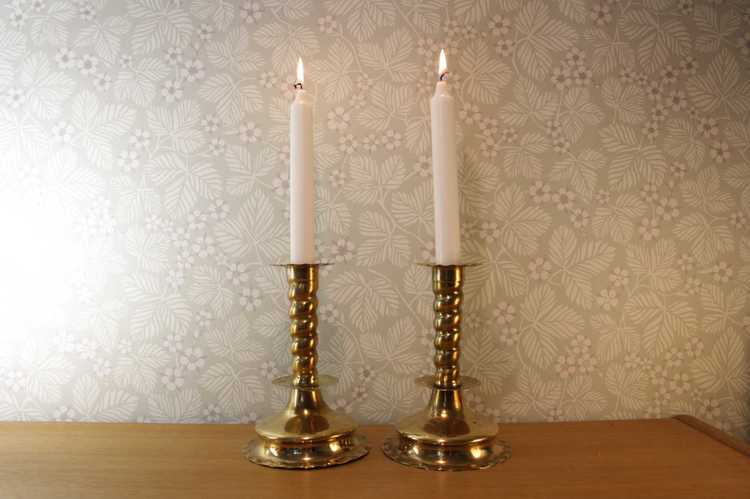 Två stycken ljusstakar i mässing med två brinnande kronljus