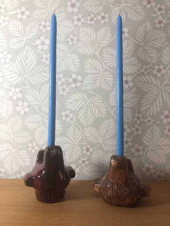 Två stycken keramikfåglar av Lars Bergsten med två stycken ljusblå stearinljus