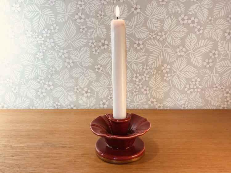 Rund vinröd ljusstake, Röd Rubin av Arthur Percy för Gefle med ett vitt brinnande kronljus