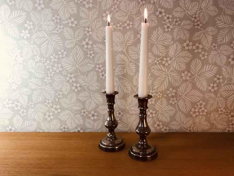 Två stycken ljusstakar i tenn med två vita brinnande kronljus