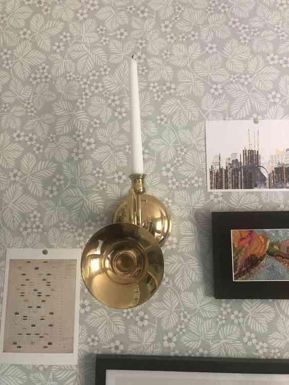Väggljusstake föreställandes ett posthorn i mässing med vitt kronljus monterad på vägg med blommig tapet fotad framifrån