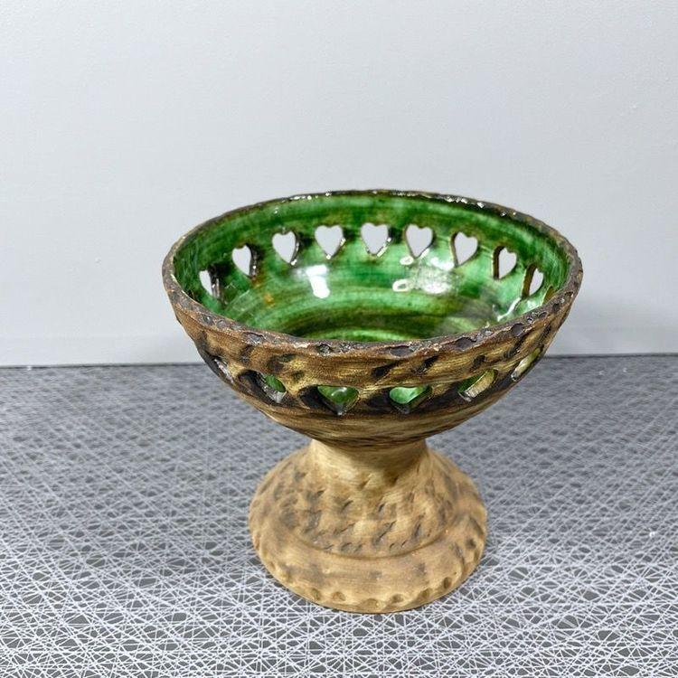 Ljusstake på fot i keramik med grön glasering och perforerad kant